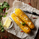 Top view of kitchen table with grilled sweet corn cob under melt - PhotoDune Item for Sale
