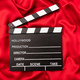 Movie cinema clapper board on red satin background, copy space - PhotoDune Item for Sale
