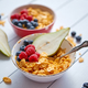Free Download Golden cornflakes with fresh fruits of raspberries, blueberries and pear in ceramic bowl Nulled