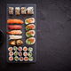 Free Download Sushi rolls set with salmon and tuna fish served on black stone board Nulled