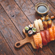 Free Download Sushi Set. Different kinds of sushi rolls on wooden serving board Nulled