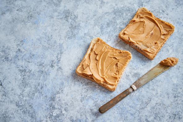 Two tasty peanut butter toasts placed on stone table - Stock Photo - Images