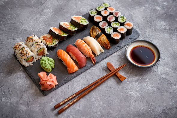 Composition of different kinds of sushi rolls placed on black stone board - Stock Photo - Images
