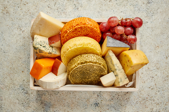 Fresh and delicious different kinds of cheeses placed in wooden crate with grapes - Stock Photo - Images