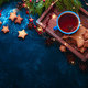 Free Download Cookies, tea and fairy lights flat lay with fir tree branches, wooden tray, anise stars, and Nulled