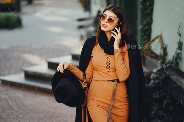 stylish girl walking through the city while using her phone - Stock Photo - Images