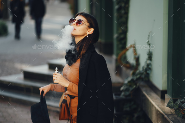 stylish girl smoking an e-cigarette - Stock Photo - Images