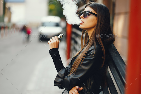 stylish girl smoking an e-cigarette - Stock Photo - Images