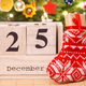 Date 25 December on calendar, gift in sock and festive tree with decoration in background - PhotoDune Item for Sale