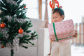 portrait of a little daughter carrying christmas present - PhotoDune Item for Sale