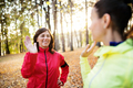 Two female runners stretching outdoors in forest in autumn nature at sunset. - PhotoDune Item for Sale