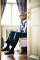 Mature businessman on a business trip in a hotel room, getting dressed. - PhotoDune Item for Sale