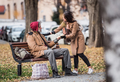 Young woman giving food to homeless beggar man sitting on a bench in city. - PhotoDune Item for Sale