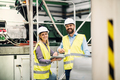 A portrait of an industrial man and woman engineer with tablet in a factory. - PhotoDune Item for Sale