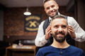 Hipster man client visiting haidresser and hairstylist in barber shop. Copy space. - PhotoDune Item for Sale