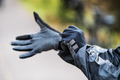 A close-up of a cyclist putting on gloves outdoors in park. - PhotoDune Item for Sale