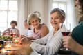 An elderly women with a family sitting at a table on a indoor family birthday party. - PhotoDune Item for Sale