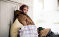 A side view of homeless beggar man sitting outdoors, leaning against a wall. Copy space. - PhotoDune Item for Sale