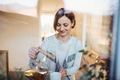 A young woman standing indoors in kitchen, pouring tea. Shot through glass. - PhotoDune Item for Sale
