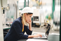 An industrial woman engineer in a factory using laptop and smartphone. - PhotoDune Item for Sale