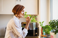 A young woman standing indoors in kitchen, smelling herbs. - PhotoDune Item for Sale