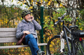 Senior man with electrobike sitting on a bench outdoors in town, using smartphone. - PhotoDune Item for Sale
