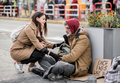 Young woman giving money to homeless beggar man sitting in city. - PhotoDune Item for Sale