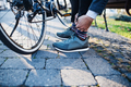 Midsection of commuter with bicycle traveling from work in city, tying shoealaces. - PhotoDune Item for Sale