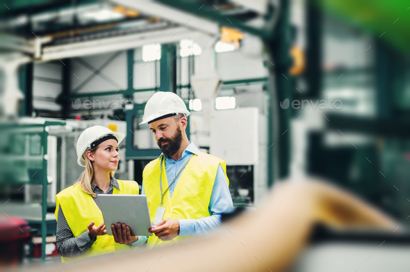 A portrait of an industrial man and woman engineer with tablet in a factory. - Stock Photo - Images