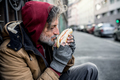 Homeless beggar man outdoors in city, holding and smelling hot-dog. - PhotoDune Item for Sale