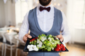 Midsection of man standing indoors in a room set for a party, holding a tray with vegetables. - PhotoDune Item for Sale