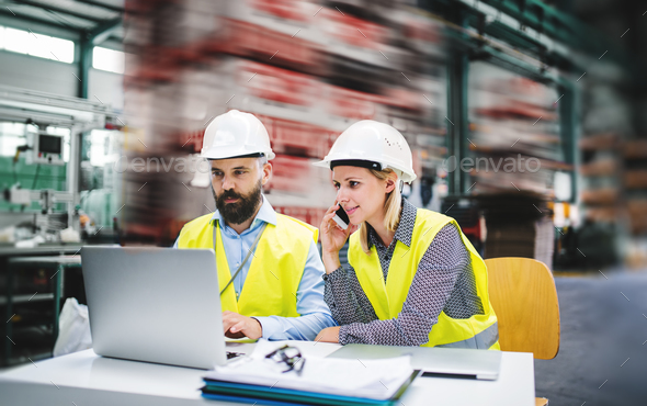 A portrait of an industrial man and woman engineer with laptop in a factory, working. - Stock Photo - Images