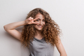 Young beautiful cheerful woman in studio, fingers forming V. - PhotoDune Item for Sale