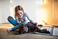 A young woman sitting indoors on the floor at home, playing with a dog. - PhotoDune Item for Sale