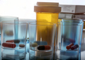 Several plastic glasses with daily medication in hospital, conceptual image - PhotoDune Item for Sale