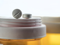 Two pills white on a bottle of medicines, conceptual image - PhotoDune Item for Sale