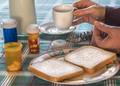 Person takes medication during breakfast, conceptual image - PhotoDune Item for Sale