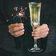 Woman in grey sweater holding sparklers and glass of champagne - PhotoDune Item for Sale