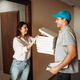 Female customer and delivery boy checks pizza - PhotoDune Item for Sale