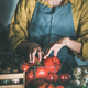 Woman in linen apron taking tomatoes out of basket - PhotoDune Item for Sale