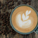 Heart shaped latte coffee with beans on wooden floor. - PhotoDune Item for Sale
