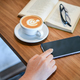 Hand using a smartphone with coffee and book on wooden table. - PhotoDune Item for Sale