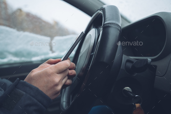 Texting in parked car while the snow is falling outside - Stock Photo - Images