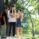 Asian boy and girl three people stand reading in garden. - PhotoDune Item for Sale