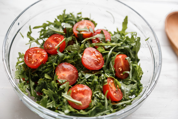 salad with arugula and tomatoes in the glass plate - Stock Photo - Images