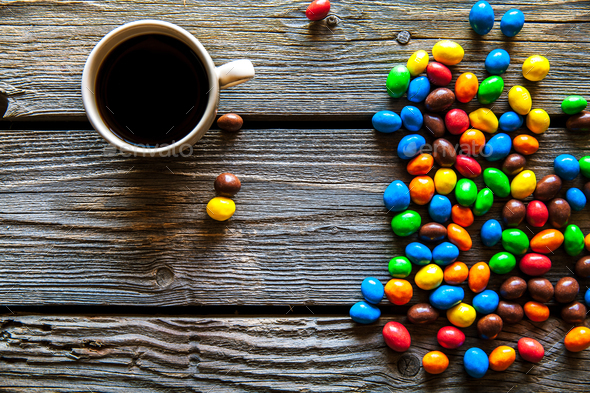 colored sweets with coffee on a wooden background - Stock Photo - Images