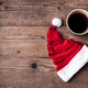 Free Download Cup of coffee and Santas hat on a wooden background, celebration Nulled