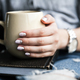 Free Download A young girl with a beautiful manicure holds a book with a cup of coffee. Fashion style Nulled