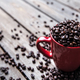 Free Download Coffee beans and red coffee cup on wooden background. Drink Nulled