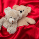 Love, concept, tight hug. Two teddy bears embracing as a couple in bed, red satin background - PhotoDune Item for Sale